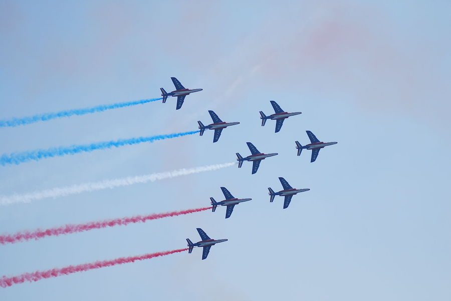 Fighter jets depicting the colors of the French flag using smoke (Photo provided by CésarOP (Own work) [CC BY-SA 3.0 (http://creativecommons.org/licenses/by-sa/3.0)], via Wikimedia Commons)